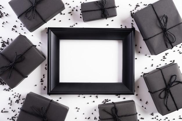 Weißer bilderrahmen mit schwarzer geschenkbox