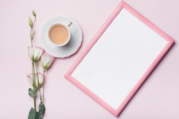 Weißer bilderrahmen; tasse tee und eustoma blüht gegen rosa hintergrund