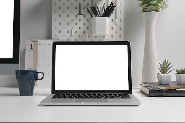 Weißer bildschirm des arbeitsbereich-laptop-computers auf kreativem schreibtisch.