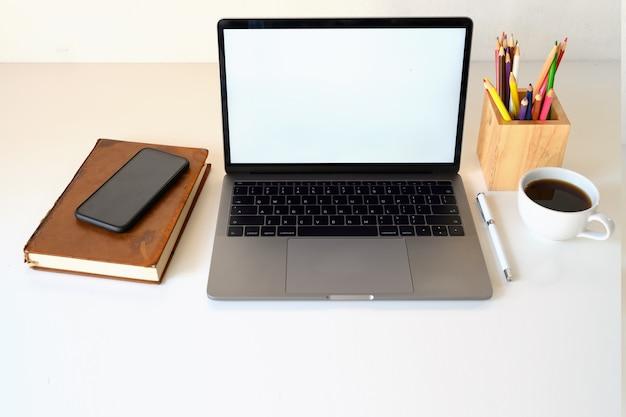 Weißer bildschirm des laptops mit designerarbeitsplatz und kopienraum.