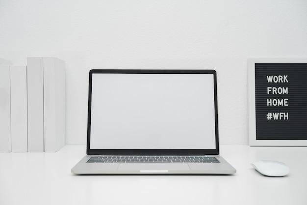 Weißer bildschirm des minimalistischen laptop-modells auf weißem tisch mit der maus. arbeit von zu hause aus konzept