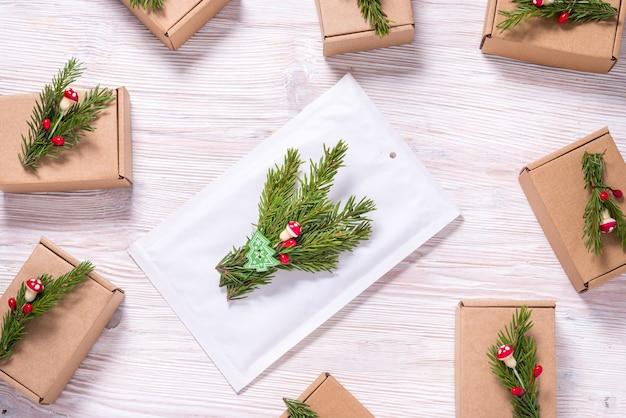 Weißer blasenumschlag abd pappkartons verziert mit weihnachtsbaumverzierung auf holz