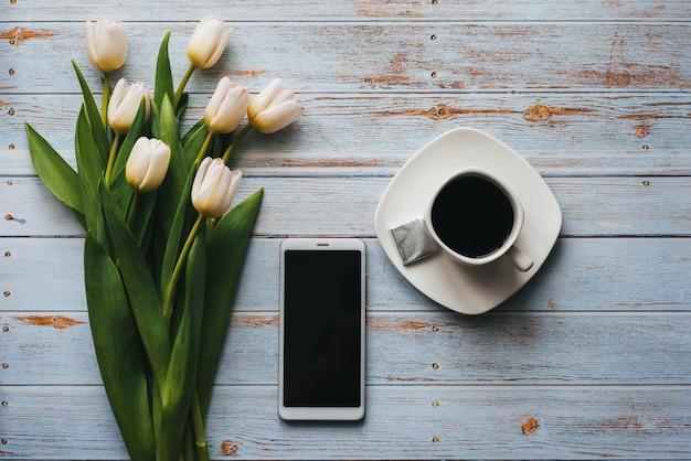 Weißer blumenstrauß von tulpen auf blauem hölzernem hintergrund mit tasse kaffee und einem smartphone