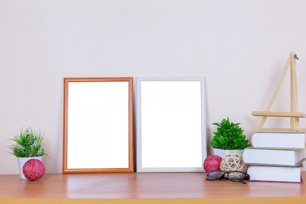 Weißer brauner bilderrahmen auf hölzerner tabelle.