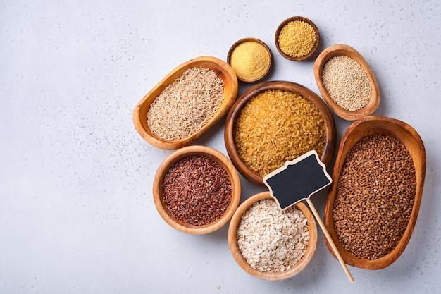 Weißer, brauner und roter reis, buchweizen, hirse, maisgrütze, quinoa und bulgur in holzschalen auf dem hellgrauen küchentisch. glutenfreies getreide. draufsicht mit exemplar