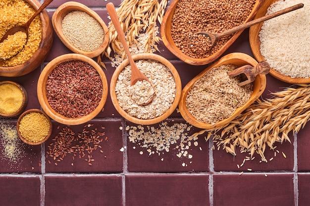 Weißer, brauner und roter reis, buchweizen, hirse, maisgrütze, quinoa und bulgur in holzschalen auf einem braunen steinküchentisch. glutenfreies getreide. draufsicht mit exemplar