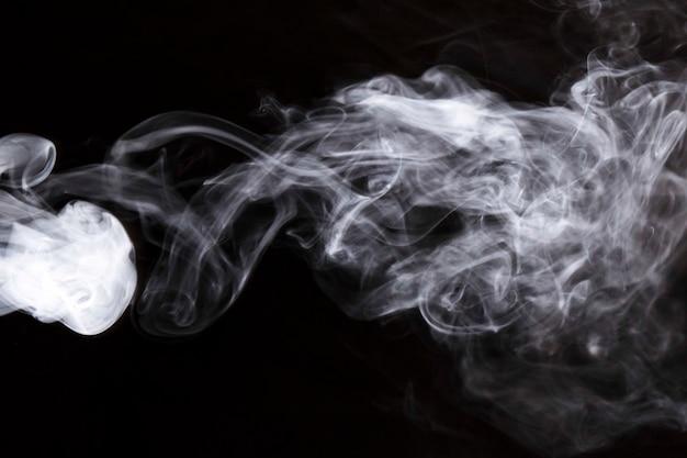 Weißer dichter wirbelnder rauch auf schwarzem hintergrund