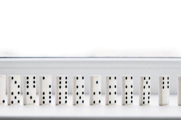 Weißer domino, dominoprinzip, auf weißem hintergrund