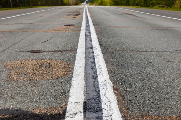 Weißer doppelter durchgehender streifen auf dem asphalt
