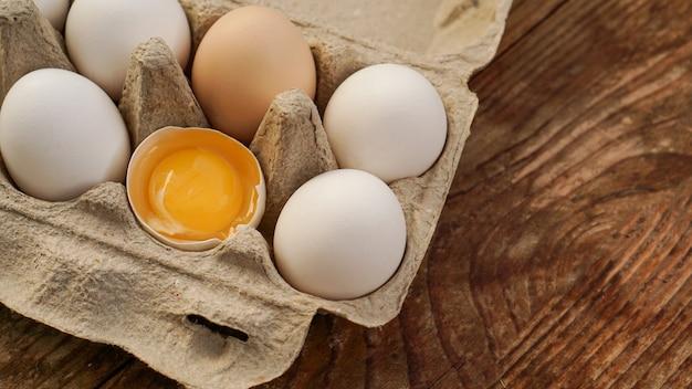 Weißer eierkarton und gebrochene eihälfte mit eigelb draufsicht auf hölzernem hintergrund. ostern und gesundes essen frühstückskonzept