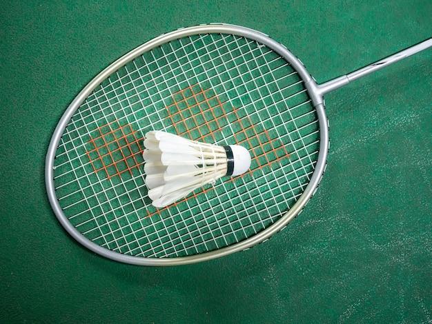 Weißer federball und schläger des federballs auf einem grünen gericht.