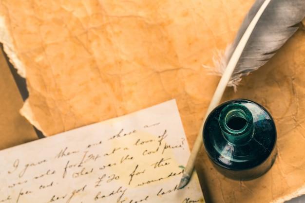 Weißer federkiel, glastintenfass und alter brief
