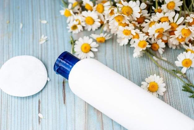 Weißer flaschenbehälter mit kräuterkamillenblumen.