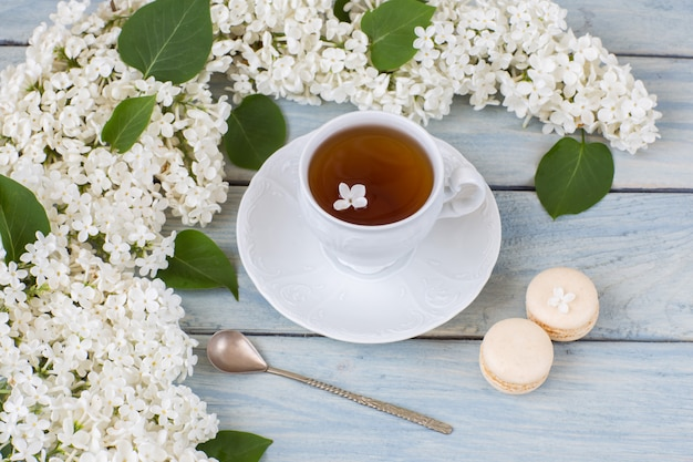 Weißer flieder, tasse tee und makronen