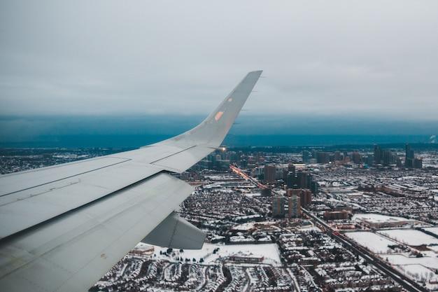 Weißer flugzeugflügel über stadt während des tages