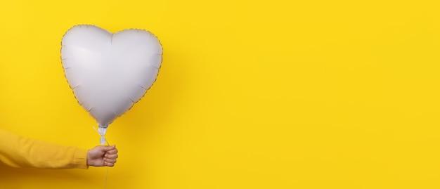 Weißer folienballon in herzform in der hand über gelbem hintergrund, panorama-layout