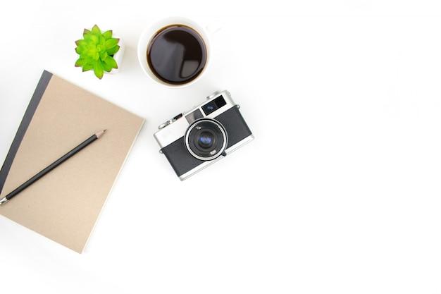 Weißer fotografschreibtisch mit filmkamera und notizbuch mit kopienraum. ansicht von oben.