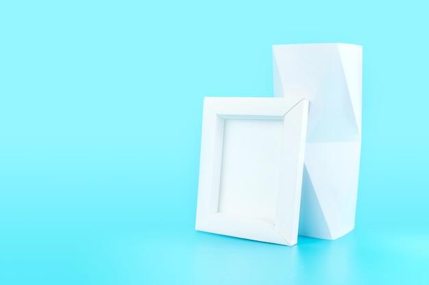 Weißer fotorahmen (hergestellt vom papier) und polygonvase auf hellblauem hintergrund
