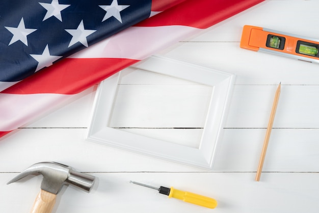 Weißer fotorahmen und amerikanische flagge auf weißem holz