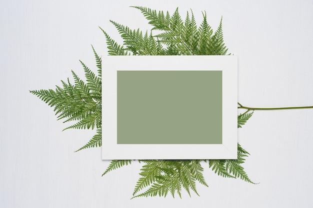 Weißer fotorahmen und grünblätter auf einem weißen hölzernen hintergrund