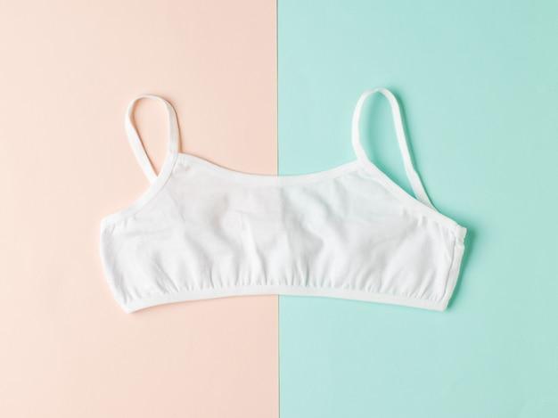 Weißer frauen-bh auf einem zweifarbigen pastellhintergrund. unterwäsche für mädchen.