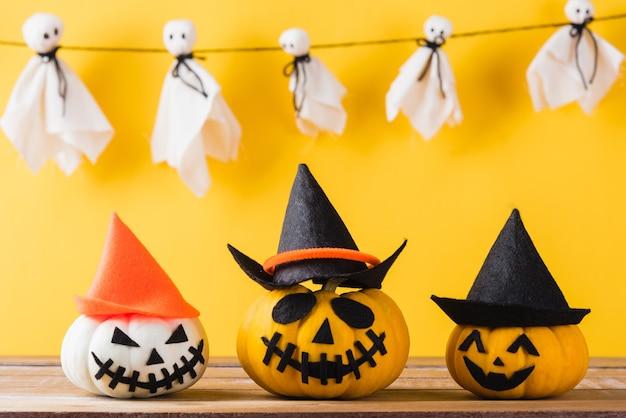 Weißer geist bastelt unheimliches gesicht hängend und halloween kürbiskopf jack laterne lächeln und spinne auf holz