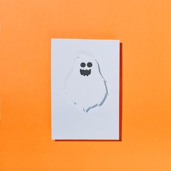 Weißer geist mit lustigem gesicht auf blatt papier