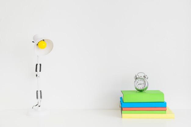 Weißer geräumiger arbeitsplatz mit bunten notizbüchern und wecker