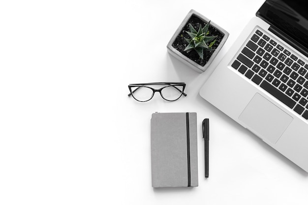 Weißer geschäftsarbeitstisch mit laptop-computer und bürobedarf auf weißem backgraund. draufsicht mit kopienraum für text, flache lage