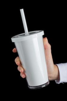 Weißer getränkeplastikbecher mit strohhalm auf schwarzer wand