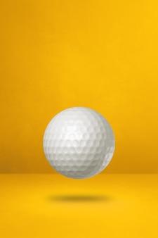 Weißer golfball lokalisiert auf gelbem studiahintergrund. 3d-illustration