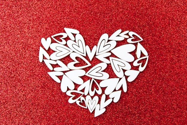 Weißer graf gemacht von den herzen auf einem roten glänzenden hintergrund. komposition über die liebe zum valentinstag.