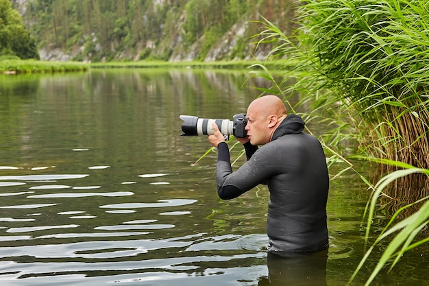 Weißer haarloser mann in wasserdichtem stoff steht im fluss mit digitalkamera in seinen händen und fotografiert wald und fluss, ökotourismus.