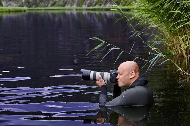 Weißer haarloser mann mit digitalkamera in seinen händen macht fotos, die im wasser des flusses sind