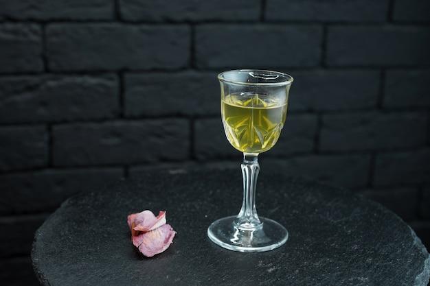 Weißer halbsüßer leckerer wein in einem glas steht auf dem tisch, der mit rosenblättern auf einem schwarzen hintergrund im restaurant verziert wird. alkoholverkostung