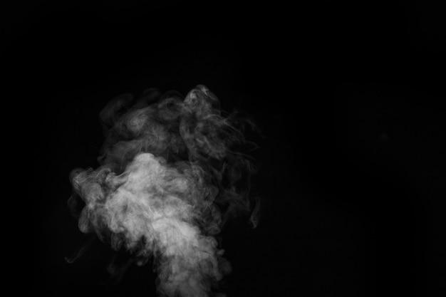 Weißer heißer lockiger dampfrauch auf schwarzem hintergrund isoliert, nahaufnahme. erstellen sie mystische halloween-fotos. abstrakter hintergrund, gestaltungselement