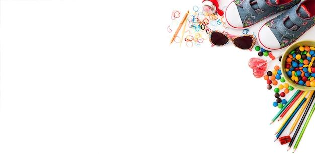 Weißer hintergrund mit bunten kindersüßigkeiten und schreibwaren mit kopienraum-kindheitskonzept