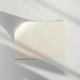 Weißer hintergrund mit einem weißen blatt papier mit seinem schatten
