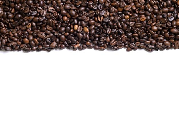 Weißer hintergrund mit kaffeebohnen auf der seite. ansicht von oben mit platz für text. stillleben. attrappe, lehrmodell, simulation. flach legen