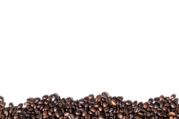 Weißer hintergrund mit kaffeebohnen auf der seite. ansicht von oben. stillleben. platz kopieren. flach liegen.