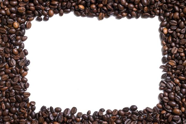 Weißer hintergrund mit kaffeebohnen auf der seite vier. ansicht von oben mit platz für text. stillleben. attrappe, lehrmodell, simulation. flach legen