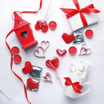 Weißer hintergrund mit roten herzen, kondomen, süsse geschenken und kerzen.
