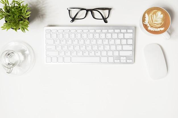 Weißer hippie-schreibtisch mit computergeräten und -versorgungen.