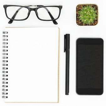 Weißer hippie-schreibtisch mit notizbuch, stift, smartphone und brillen.