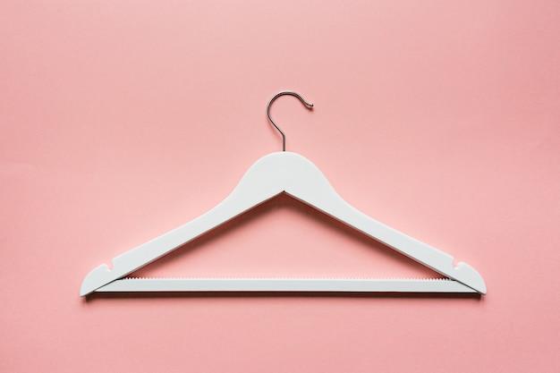 Weißer hölzerner aufhänger auf rosa