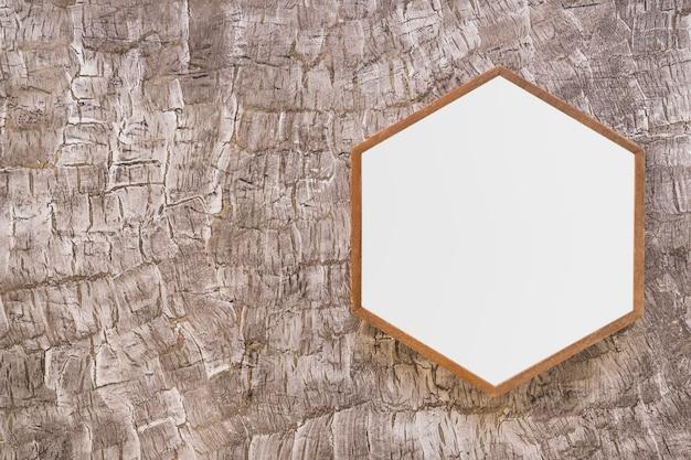 Weißer hölzerner hexagonrahmen auf gemalter wand