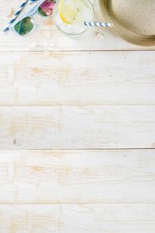 Weißer hölzerner hintergrund des gefrorenen getränks der sommerferienferienkonzepthintergrundhut-sonnenbrille (limonade mojito)