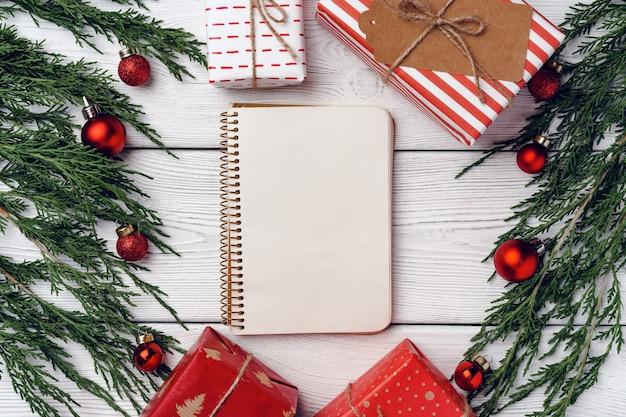 Weißer hölzerner hintergrund mit nadelzweigen und weihnachtsdekorationen, draufsicht