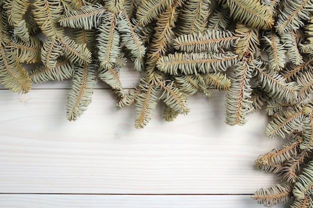 Weißer hölzerner hölzerner hintergrund mit christbaumzweigen und spielzeugen