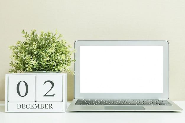Weißer hölzerner kalender mit schwarzem wort am 2. dezember mit weißer leerstelle in der mitte des computernotizbuches auf weißem hölzernem schreibtisch